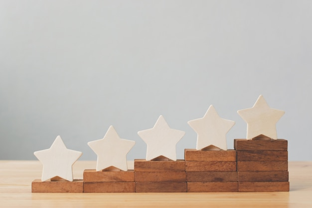 Wooden five star shape on table. the best excellent business services rating customer experience concept Premium Photo