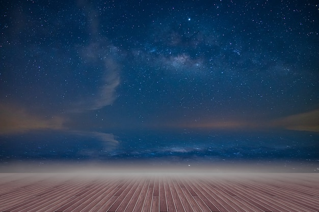 Wooden floor and backdrop of the milky way sky at night Premium Photo