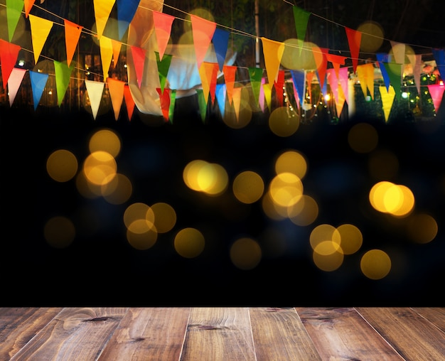 Wooden floor and colorful flags over bokeh for night party decoration background Premium Photo