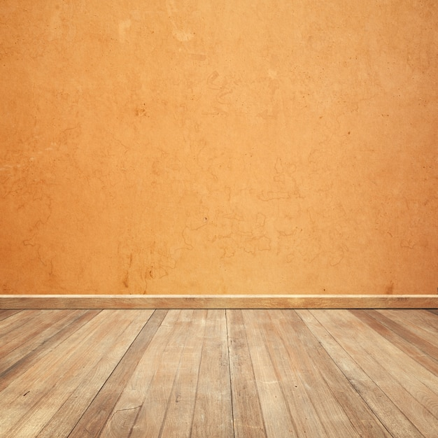 Wooden floor with an orange wall background Free Photo