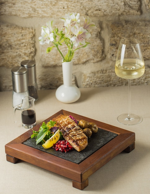 Wooden food stand with grilled fish fillet and vegetables Free Photo