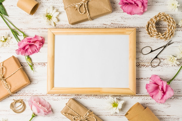 Wooden frame; gifts; pink eustoma flowers and scissor on wooden surface Free Photo