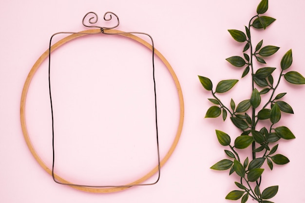 Wooden frame near the artificial green plant on pink backdrop Free Photo