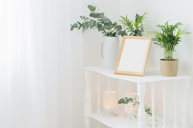 꽃과 식물으로 빈티지 화이트 선반에 나무 프레임 프리미엄 사진