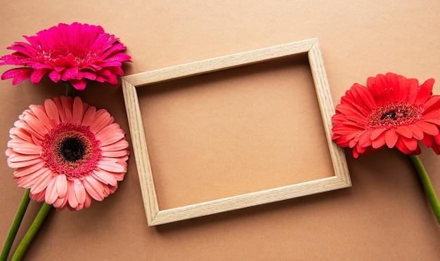 明るい茶色の背景、上面図、コピースペース、フラットレイの美しいガーベラの花に囲まれた木製フレーム。 Premium写真