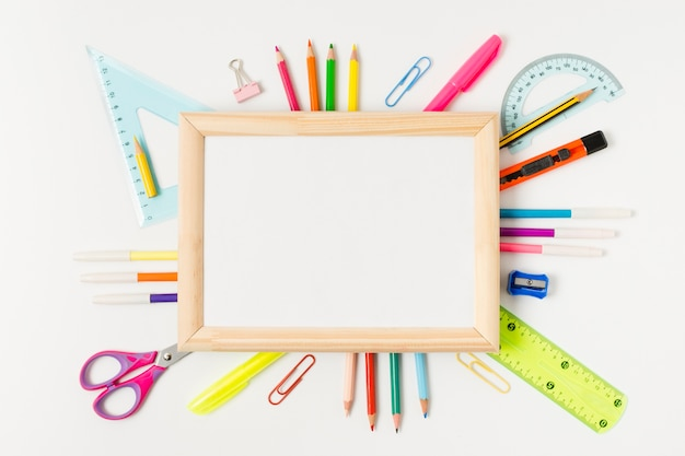 Wooden frame surrounded by school accessories Free Photo