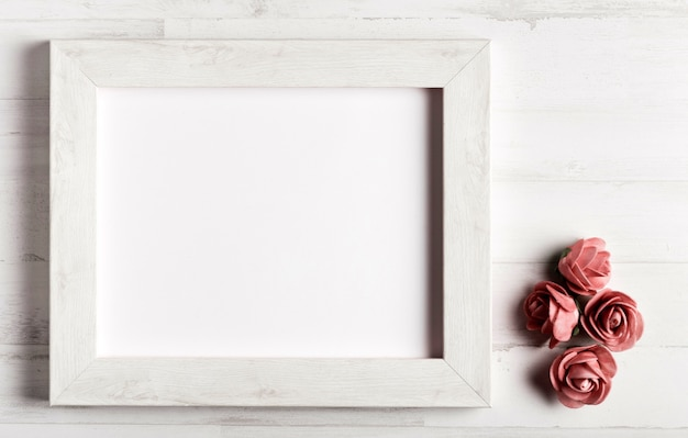 Wooden frame with roses beside Free Photo
