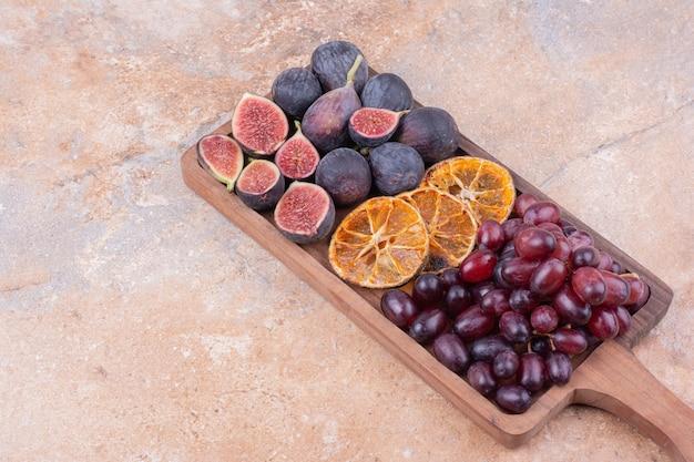 Piatto di frutta in legno con fichi, bacche d'angolo e fette d'arancia secche. Foto Gratuite