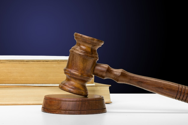 Wooden gavel and books on wooden table Premium Photo