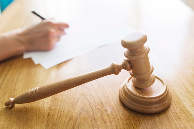 Wooden gavel in front of judge writing on document Premium Photo