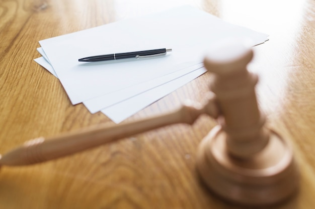 Wooden gavel in front of pen and blank papers Free Photo