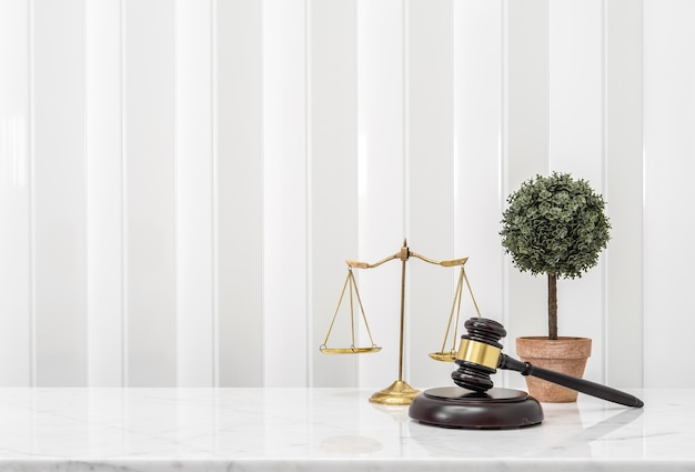 Wooden Gavel And Lawyer Balance Scales On White Marble Counter Table