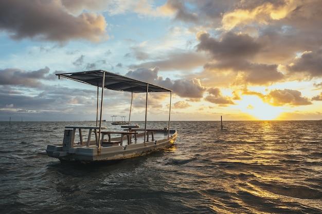 曇り空と日没時の日光の下で海に木製の手作りボート 無料写真