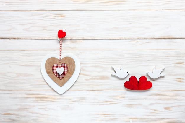 Деревянное сердце на веревке и статуэтки голубей с сердечками. Premium Фотографии