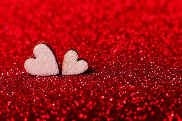 Wooden hearts on brilliant red bright background for a festive decoration Premium Photo