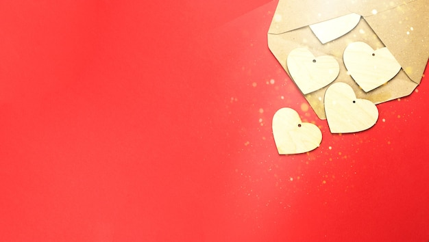 Wooden hearts spill out of an open envelope on a red background Premium Photo