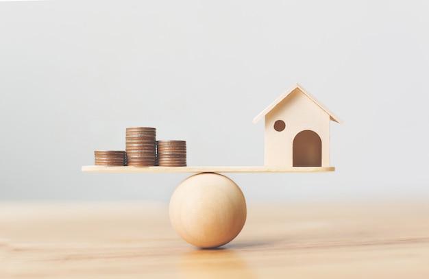 Деревянный дом и деньги монеты стека на деревянный масштаб. инвестиции в недвижимость и ипотека концепция финансовой недвижимости Premium Фотографии