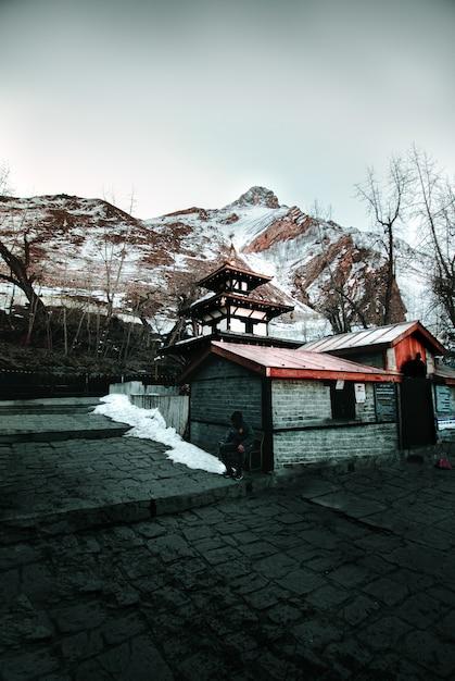 冬の雪に覆われた丘に対する木造住宅 無料写真