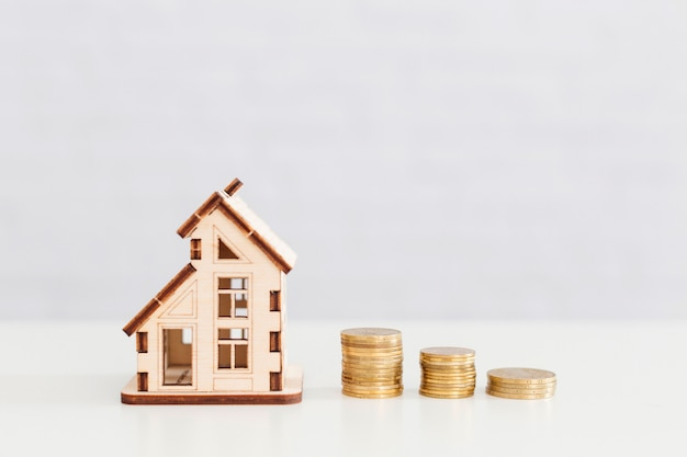 Wooden house and coins stack Free Photo