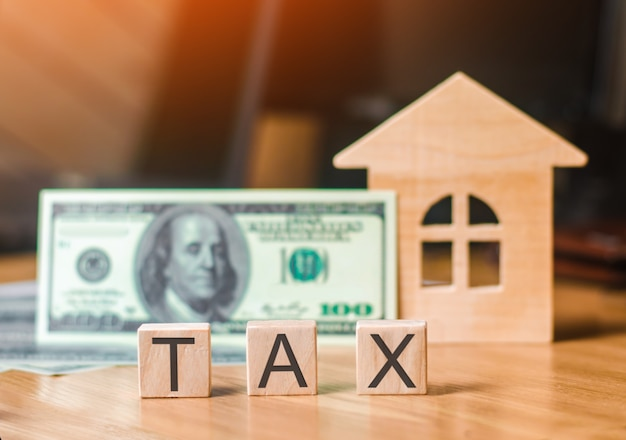 Wooden house and a bill of one hundred dollars, inscription taxes. concept of property tax Premium Photo