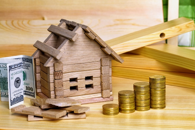 Wooden house block with coins. (finance, property and house loan concept). house miniature with pile of coins. money for the building and details of the new building.buying a new home. Premium Photo
