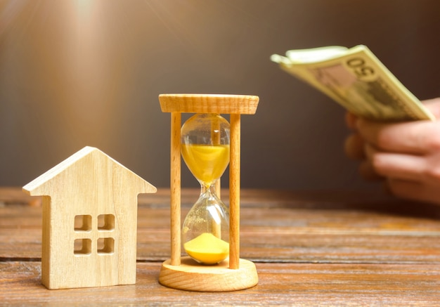 Wooden house and clock. businessman counting money Premium Photo
