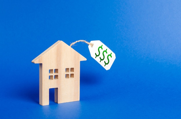Wooden house figure and price tag. Premium Photo