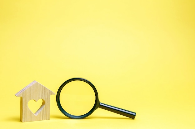 Wooden house with a heart and a magnifying glass Premium Photo