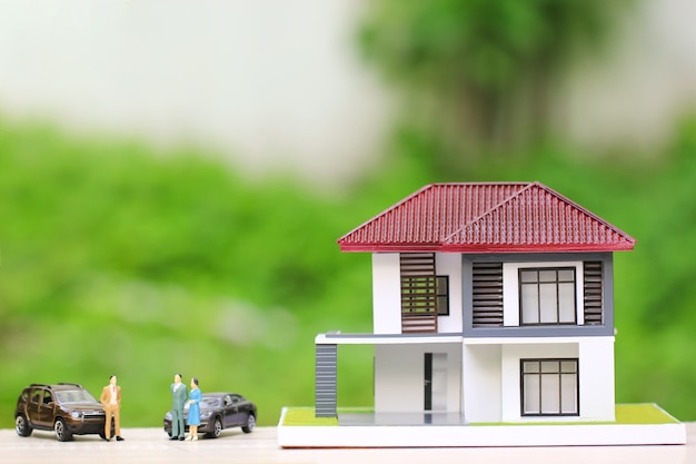 Wooden house with miniature people standing and car Premium Photo