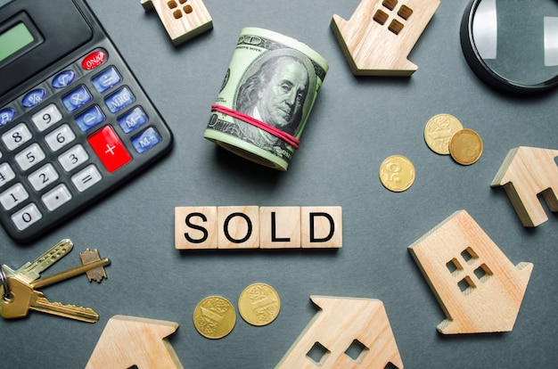 Wooden houses, a calculator, keys, coins and blocks with the word sold. Premium Photo