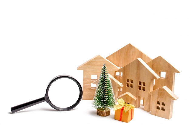 Wooden houses and christmas tree and magnifying glass. Premium Photo