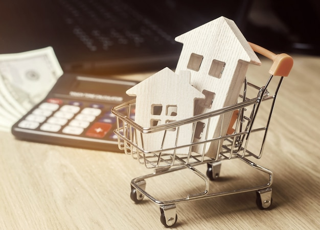 Wooden houses in a supermarket trolley, money and a calculator. real estate market analytics. Premium Photo