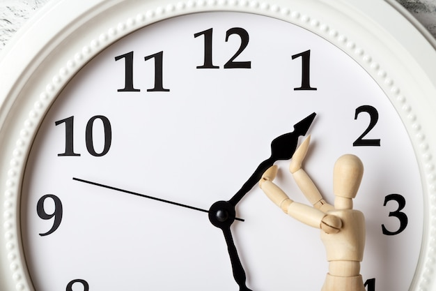 Wooden human figure trying to stop the arrow of the clock Premium Photo