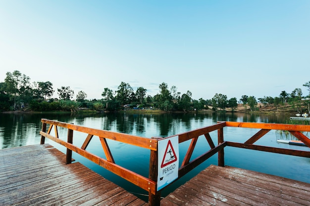 Wooden jetty with danger sign jumping into the water Premium Photo