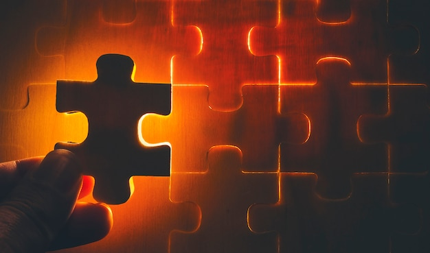 The wooden jigsaw puzzle is missing pieces that are ready to light.it is a business concept in component success. Premium Photo