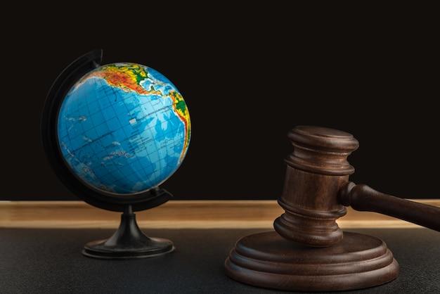 Деревянный молоток судьи и глобус. Premium Фотографии