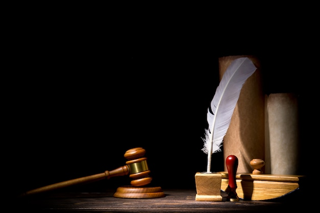 Wooden judge gavel hammer, old inkstand with feather quill, blotter, seal near scrolls Premium Photo