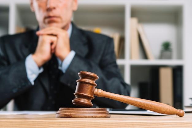 Деревянный судейский молоток на столе перед адвокатом Premium Фотографии