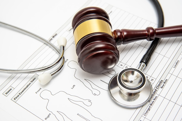 A wooden judge gavel and stethoscope on a medical chart. Premium Photo