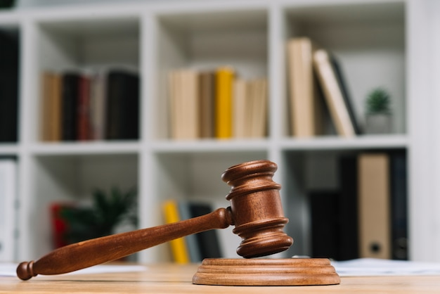 Wooden judge gavel on table in front of bookshelf Free Photo
