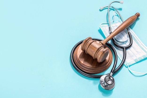 Деревянный молоток судьи с медицинской маской и стетоскопом доктора на синем фоне. законодательство в области здравоохранения и медицинская концепция Premium Фотографии