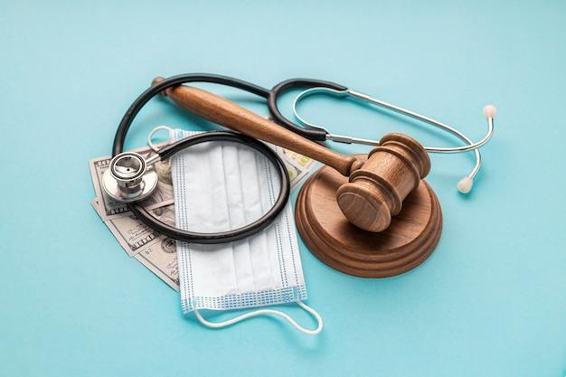 Деревянный молоток судьи с медицинской маской, стетоскопом врача и деньгами на синем фоне. законодательство в области здравоохранения и медицинская концепция Premium Фотографии