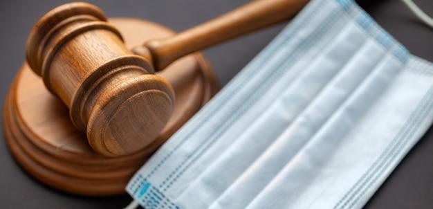 Деревянный молоток судьи с медицинской маской. законодательство в области здравоохранения и медицинская концепция Premium Фотографии