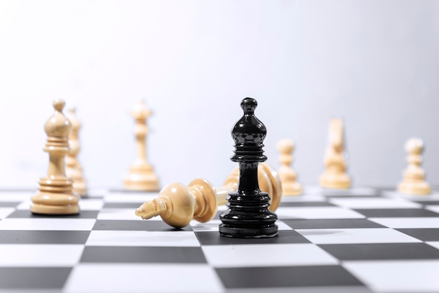 Wooden king chess piece defeated by black bishop chess piece Premium Photo
