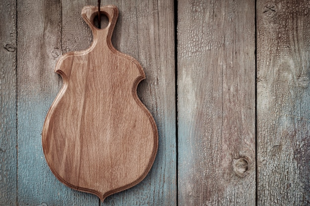 Wooden kitchen board hanging on a wooden old wall Premium Photo
