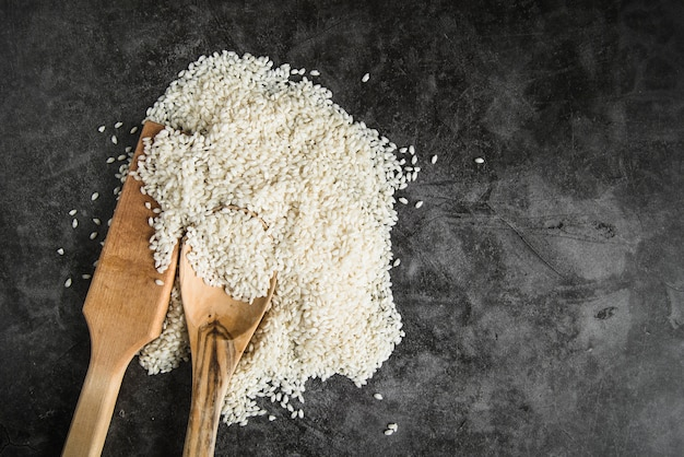 Wooden kitchen paddle and spoon with white rice Free Photo