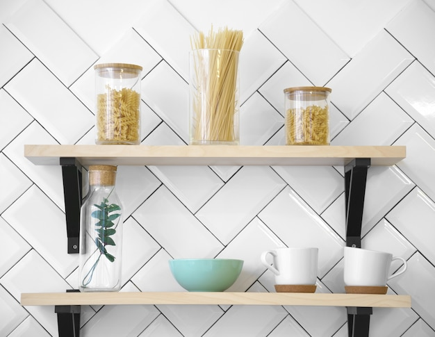 Wooden kitchen shelves with cups and glass jars Premium Photo