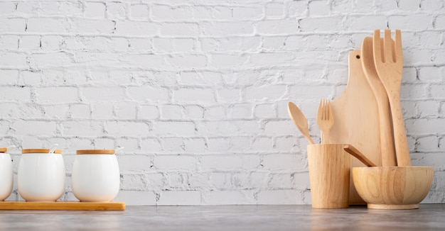 Wooden kitchenware and cups on white brick wall texture background. Premium Photo