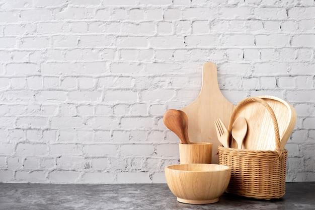 Wooden kitchenware on white brick wall texture background, copy space. Premium Photo