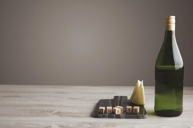 슬라이스 염소 치즈와 흰색 나무 테이블과 회색 중립 배경에 대리석 돌 보드에 고립 절반 빈 녹색 와인 주스 포도 병 근처 나무 편지 벽돌 무료 사진